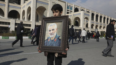 A boy carries a portrait of Iranian Revolutionary Guard Gen. Qassem Soleimani, who was killed in a U.S. airstrike in Iraq.