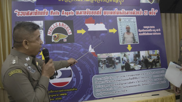 An immigration officer uses a timeline information board describing details of Australian national Luke Anderson during a press conference at the Immigration Bureau in Bangkok.