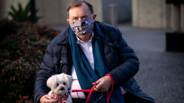Melbourne-based Harold Mitchell, photographed wearing a mask in line with government rules in the pandemic and with his dog Lilly, is calling for an investigation in relation to ASIC's conduct of this case.