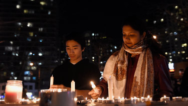 People light candles at a makeshift memorial to the victims in Toronto..
