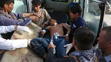 A man injured in the bombing in the Shiite neighbourhood of Dasht-i Barcha is placed in an ambulance.