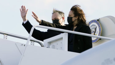Vice-President Kamala Harrisand her husband, Doug Emhoff, wave as they board Air Force Two at Andrews Air Force Base, Maryland.