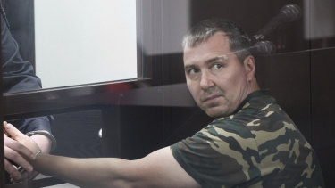 Alexander Popov, a man who was arrested on suspicion of murder sits behind the glass in a courtroom in the city of Gorodets, 60 km north-west of Nizhny Novgorod, Russia.