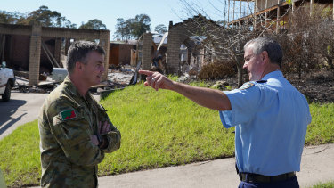 Assistant Commissioner Mick Willing and Brigadier Mick Garraway discuss clean-up measures at a bushfire-ravaged town.