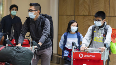 Passengers arrive at Sydney Airport on Monday wearing masks to avoid contact with the virus.