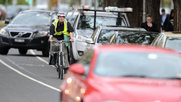 A cyclist negotiates traffic on busy St Kilda Road.