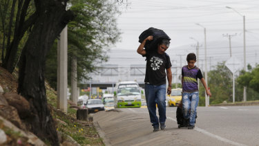 Venezuelan father Darwin Zapata walks with his 12-year-old son, as they make their way to Peru.