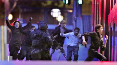 Hostages flee after police storm the cafe following the execution of Tori Johnson.