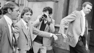 October 1981: Christopher Dale Flannery (second from left) is led handcuffed into Melbourne's City Watch House to be charged with the murder of Roger Wilson.