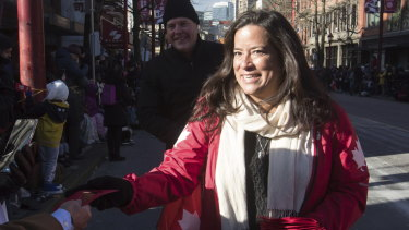 Veterans Affairs Minister Jody Wilson-Raybould, right, hands out lucky red envelopes during a Chinese New Year Parade in Vancouver on Sunday.