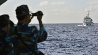 Vietnamese sailors watch the approach of a Chinese coast guard vessel.