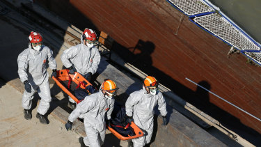 Members of a South Korean rescue team carry a body from the sightseeing boat after it was lifted out of Danube River on Tuesday.