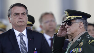 Brazil's President Jair Bolsonaro, left, receives military honours on Friday.
