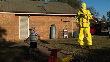 Harvey Kleinig, 2, runs away scared from his grandfather, Jeff Kleinig, who is wearing his tongue-in-cheek protective suit he designed in response to the coronavirus pandemic, in Dubbo.