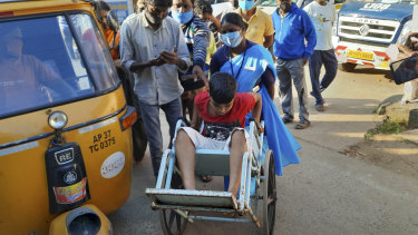 A young patient is brought in a wheelchair to the district government hospital in Eluru.
