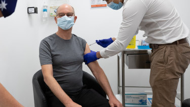 Vaccination style: Chief Medical Officer Paul Kelly receives a dose of the Pfizer vaccine on Sunday.