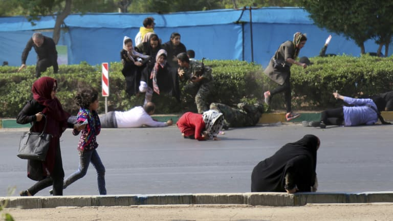 Civilians try to take shelter in a shooting scene, during a military parade marking the 38th anniversary of Iraq's 1980 invasion of Iran, in the southwestern city of Ahvaz.