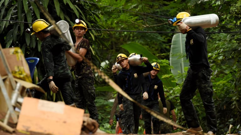 Thai army soldiers carry oxygen cylinders out of the cave on Saturday.
