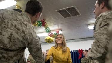 First lady Melania Trump talks with troops at a dining hall.