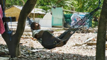 A villager from Nipah in North Lombok rests in a hammock in front of the ruins of what used to be his big family house.