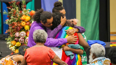 Mabo family members comfort each other during the state funeral held for Dr Ernestine 'Bonita' Mabo AO at Townsville Stadium.