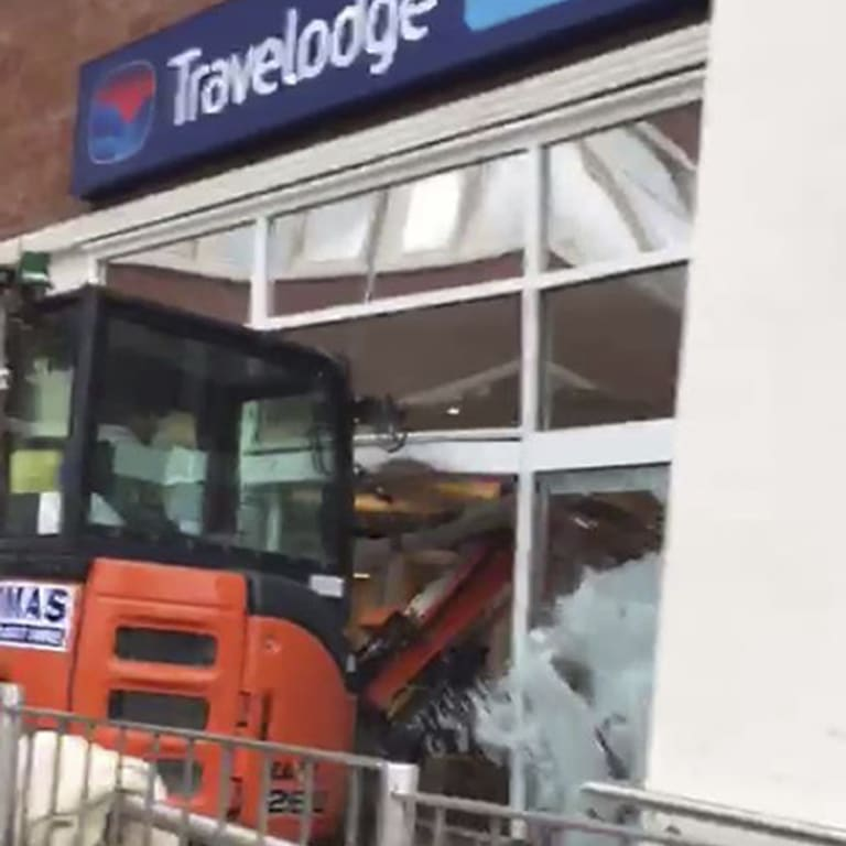 Wreaking havoc: A bulldozer drives through the front of a Travelodge.