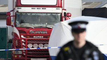 Police stand guard at the site where 39 bodies were discovered in a lorry.