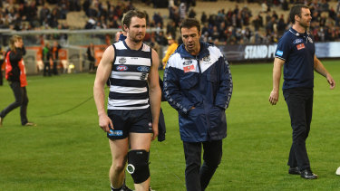Patrick Dangerfield talks with coach Chris Scott after injurying his knee against the Bombers.