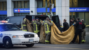 """Officials carry a body into a vehicle after the incident police said """"definitely looked deliberate""""."""