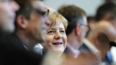 German Chancellor Angela Merkel smiles as she attends a faction meeting of the Christian Union parties, the Christian Democratic Union, CDU, and Bavarian's Christian Social Union, at the Reichstag building in Berlin, on Monday.