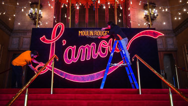 Nelson Pollard (left) and Matt Spargo install a recreation of Baz Luhrmann's glowing red L'amour sign at the Regent to celebrate the return of theatre to Melbourne.