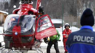 A police officer looking at an Air Zermatt helicopter landing after searching for survivors of an earlier avalanche in early April.