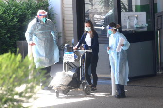 A guest is evacuated from the Holiday Inn quarantine hotel on Wednesday morning.