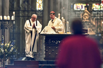 German Cardinal and Archbishop Rainer Woelki, right, celebrate the first church service at Germany's most famous Cologne Cathedral since the ban due of the coronavirus pandemic.