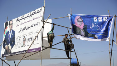 Afghan men install election posters of parliamentarian candidates during the elections campaign for the election in Kabul, Afghanistan.