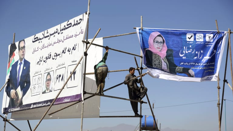 Afghan men install election posters of parliamentary candidates during election campaign for election in Kabul, Afghanistan.