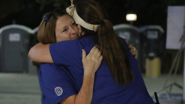 Volunteers Denise Buessing, left, and Marsha Struzik embraces following a deadly shooting at the Gilroy Garlic Festival in California.