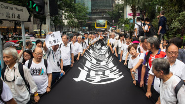 Demonstrators carry a banner during a protest organised by the elderly in the central district of Hong Kong.
