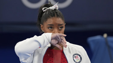 Simone Biles watches on after she exited the team final.
