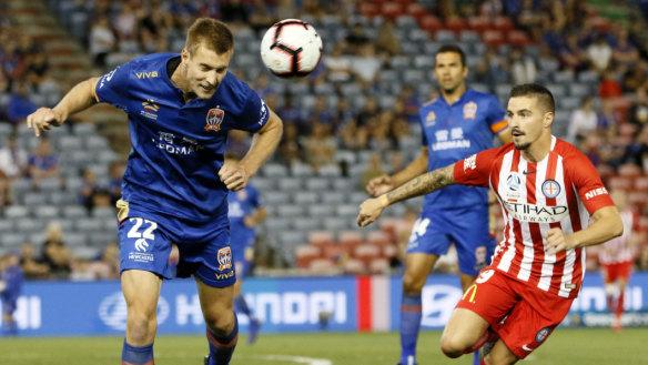 Newcastle defender Lachlan Jackson clears with dangerous City striker Jamie MacLaren  lurking.