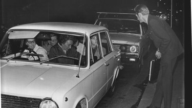 A lucky hitchhiker scores a lift in an already crowded car on Clarence Street, Sydney. May 21, 1969.