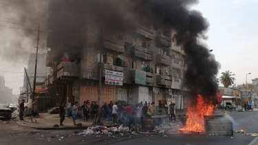 Anti-government protesters set a fire and block roads in Baghdad, Iraq.