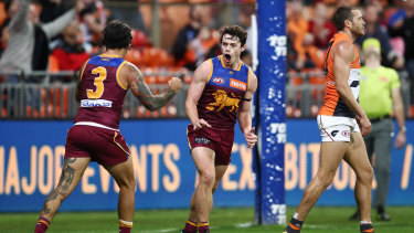 Roar power: Lachie Neale (centre) notches another goal for the Lions during their round 16 win over GWS at Giants Stadium.