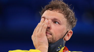 Dylan Alcott wipes away a tear on the podium in Tokyo.