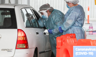 Nurses wearing face shields and surgical masks swab drivers for COVID-19 at a drive-through clinic in Geelong.