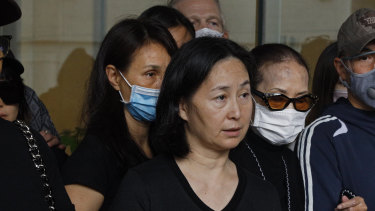 Stanley Ho's daughter, Pansy (centre), speaks alongside other family members outside a hospital in Hong Kong on Tuesday.