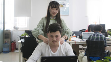 Shen Yue massages the shoulders of one of her colleagues at Chainfin.com in Beijing.