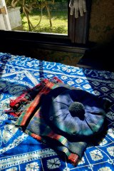 The artist's signature tartan scarf and tam-o-shanter rest on a bed.