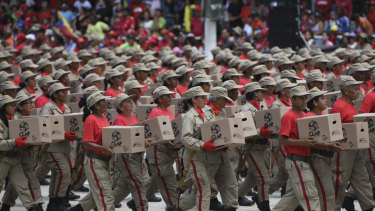 Members of the National Bolivarian Militia march with government issue food distribution boxes, known by the Spanish acronym CLAP, during a Venezuela Independence Day military parade in Caracas.
