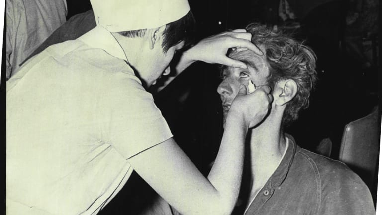 A nurse brushes ashes from the eyes of a weary firefighter at Springwood, November 29, 1968